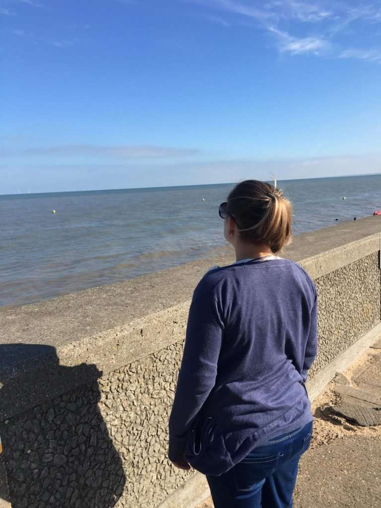 Image of Lisa facing away from the camera looking out to sea, hoping that the sea would help reduce the panic