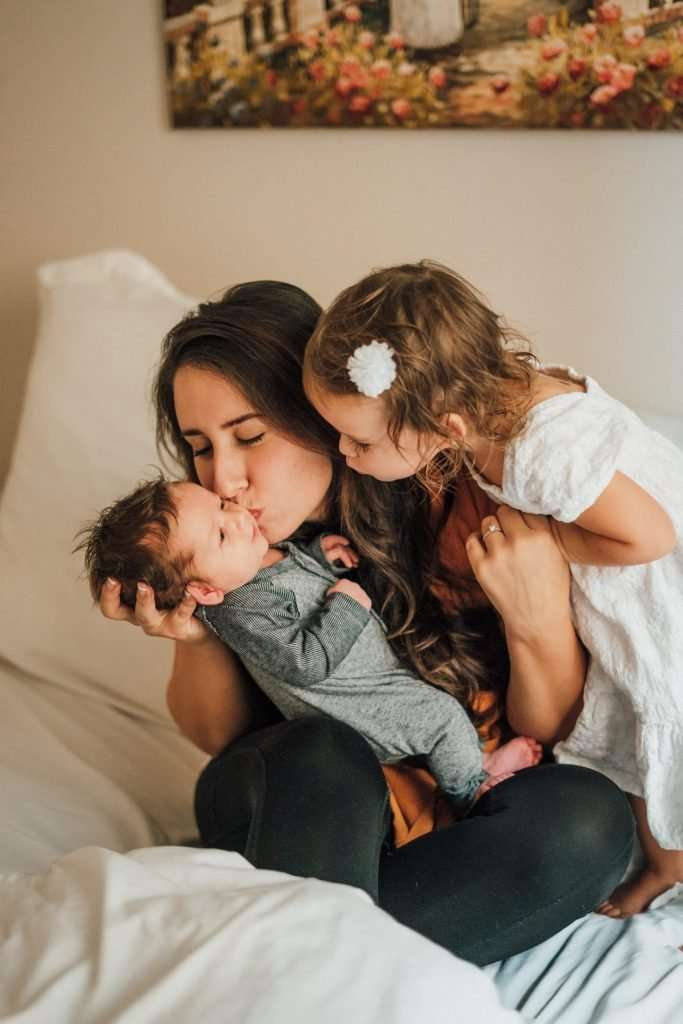 A mother sitting a bed, hold a newborn child and kissing them while a little girl leans over