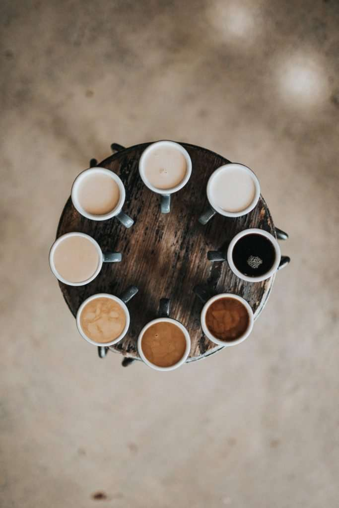 Lots of tea and coffee in a circle on a wooden table