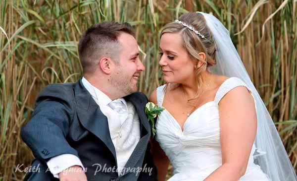 Lisa and Daz sitting in tall grass on our wedding day - Love