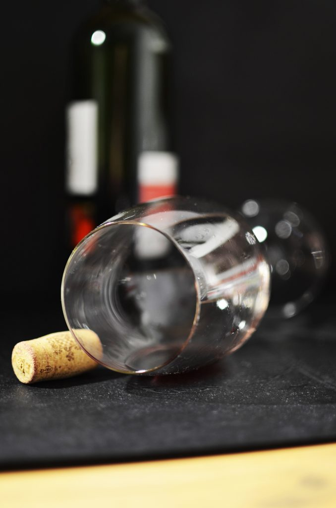 Empty wine glass fallen over with lipstick on the rim and a cork next to it