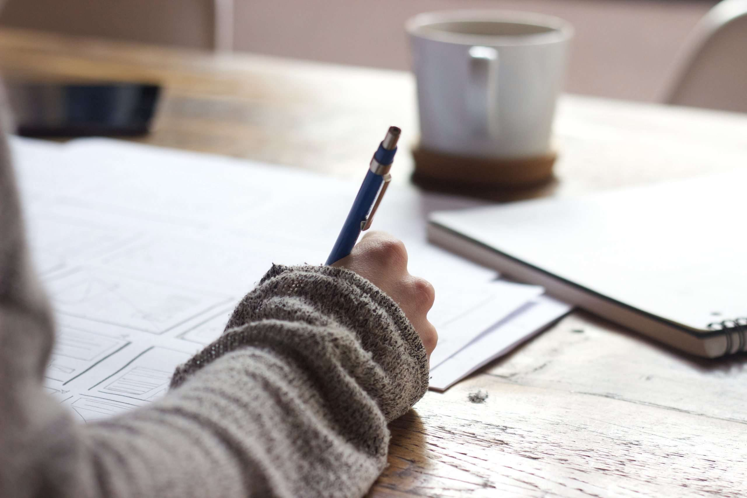 A woman in a light brown jumper is holding a pen and writing. she is sat at a wooden table and there is a cup of coffee in front of her