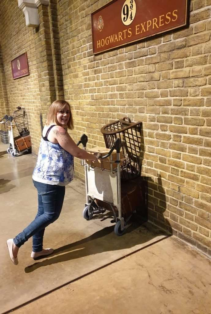 Lisa on the Harry Potter tour pushing a trolley through platform 9 3/4