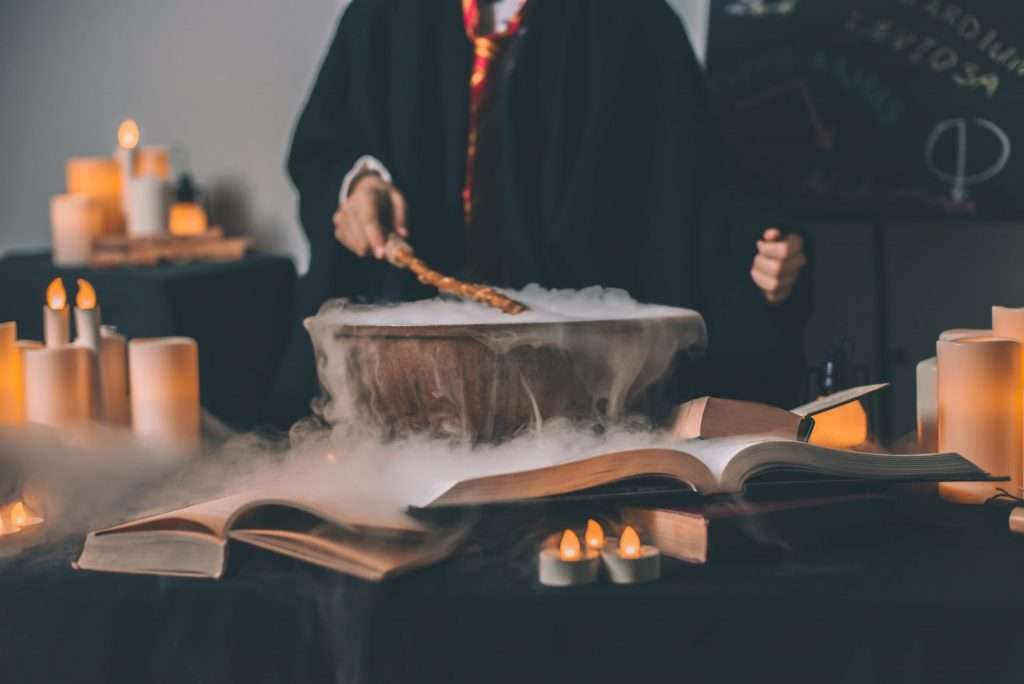 A person wearing wizard robes is using a wand to stir a pot which is poring with dry ice. There are fake candles and books all over