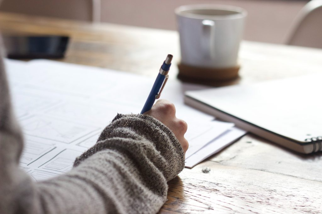 On a wooden desk are a notebook, some papers and a coffee mug. There is a hand holding a pen, writing