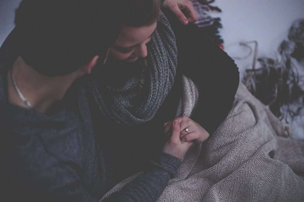 A couple are sat down cuddling. They are under a blanket and the woman is wearing a grey scarf