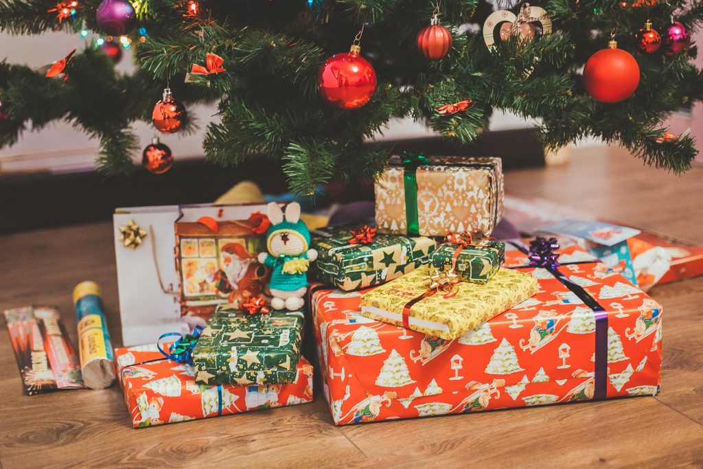 Lots of different sized Christmas presents wrapped in different paper are sitting under a Christmas tree