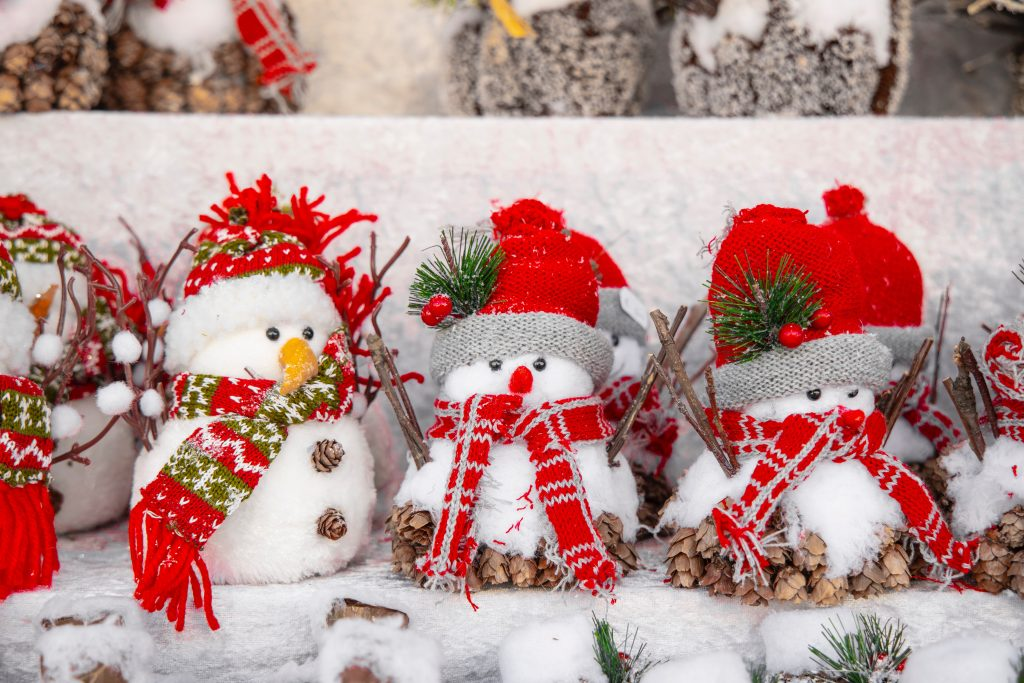 Little fake snowmen in red hats and scarfs are stood in a line