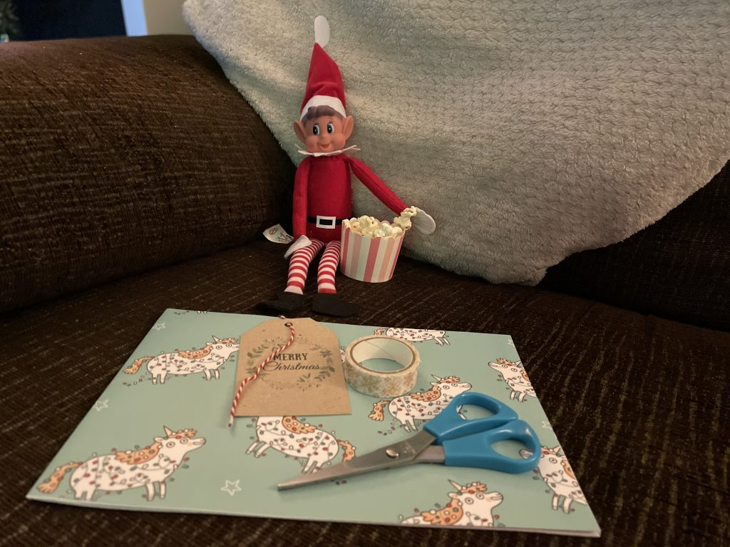Elf on the shelf is sat on a brown sofa with a white cushion. He has a tiny bowl of popcorn and there is wrapping paper, scissors and tape in front of him