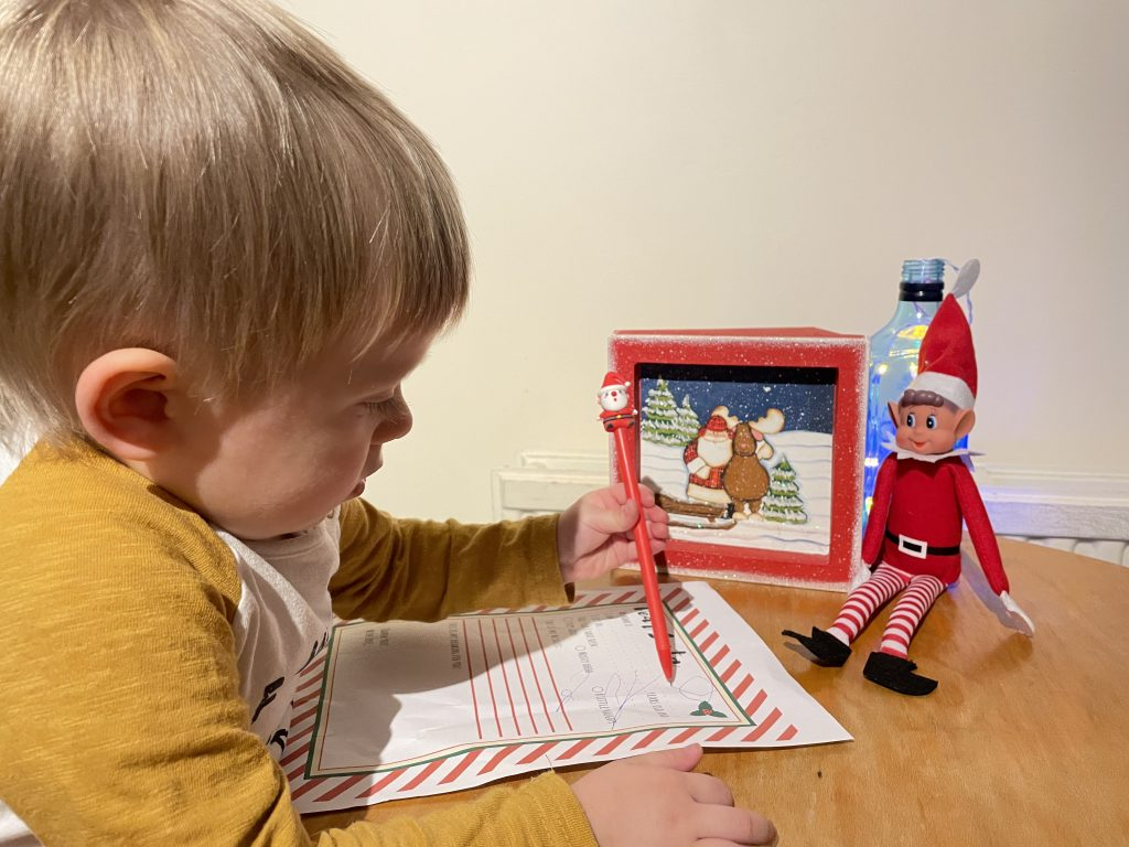 Little J is sat at a wooden table and is holding a pen with Santa on the top. He is drawing on a piece of paper. Elf on the shelf is sat on the table with him