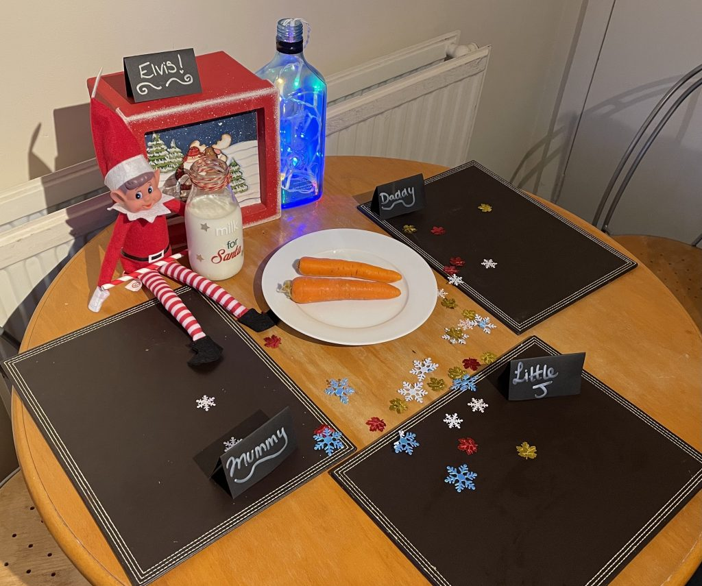 Elf on the shelf is sat on a wooden table. On the table is 3 brown placemats with name places. There is a bottle of milk on the table for Santa and 2 carrots on a white plate. There are decorative snowflakes and leaves on the table