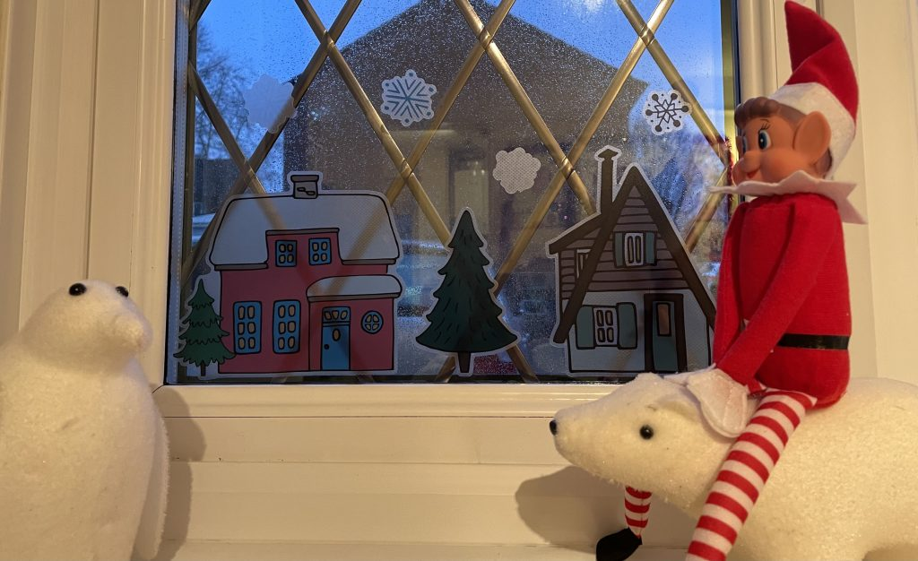 Elf on the shelf is sat on a small decorative polar bear. There is a decorative white penguin with them. They are next to a window looking at Christmas stickers