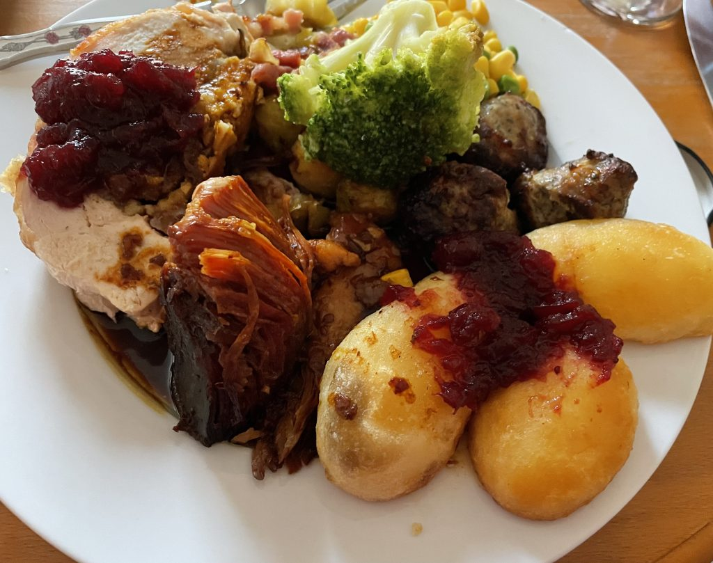 Christmas dinner on a white plate. Gammon, Roast potatoes, broccoli, stuffing and cranberry sauce.