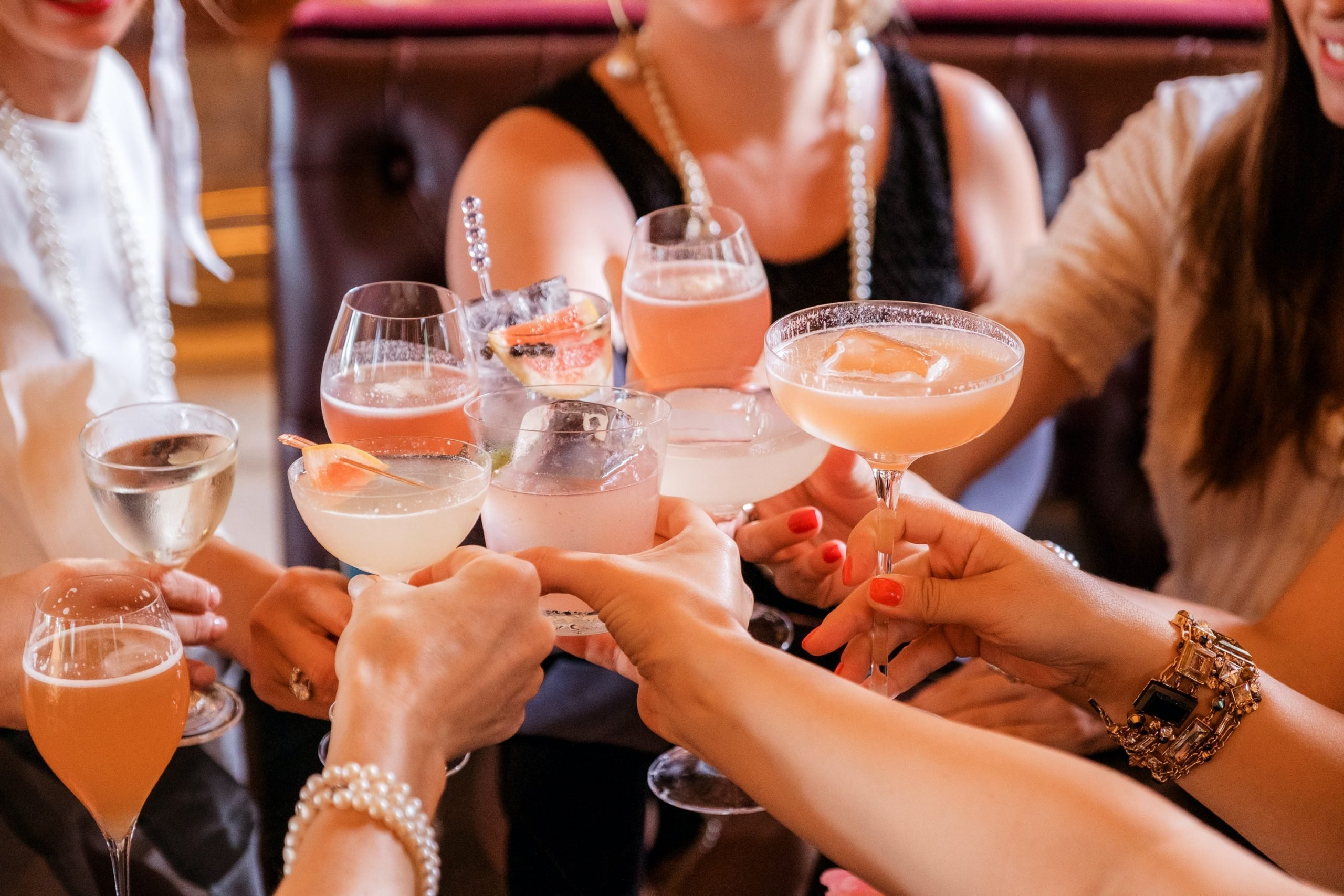 Lots of people are standing in a circle all holding different types of glasses and cocktail drinks. You can only see their arms and they look dressed up as if they are at a party