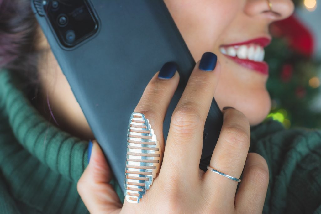 Close up of the bottom half of a woman's face. She has her head turned to the side and is smiling. She is wearing red lipstick and has a nose ring. She is wearing a green polo jumper and is holding a mobile to her ear. She has a large silver ring on her index finger and a small silver ring on her fourth finger