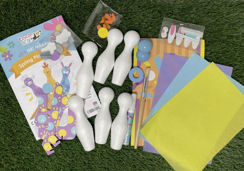 On a grass surface is 6x bowling pin halves Bowling ball halves Bowling lane 3x tissue paper in purple, blue and yellow Ramp Pin decorations Glue Double-sided sticky pads Paintbrush