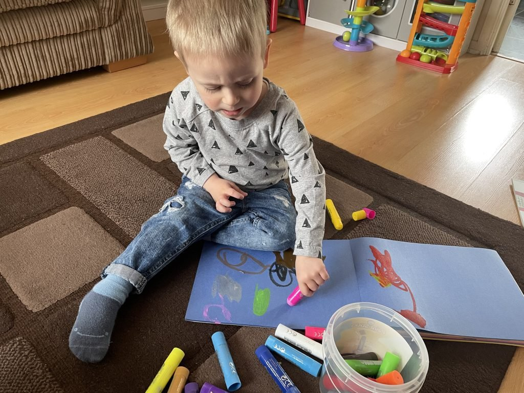 Little J is wearing a grey top and jeans. He is sat on the floor on a brown rug and is using Little Brian Paint Sticks to draw on blue paper