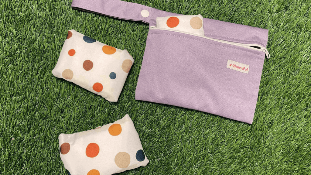 A Purple Cherriful carry bag is resting on grass with a spotted Cherriful reusable pad folded up, poking out. There are two cheerful reusable pads folded up next to the bag