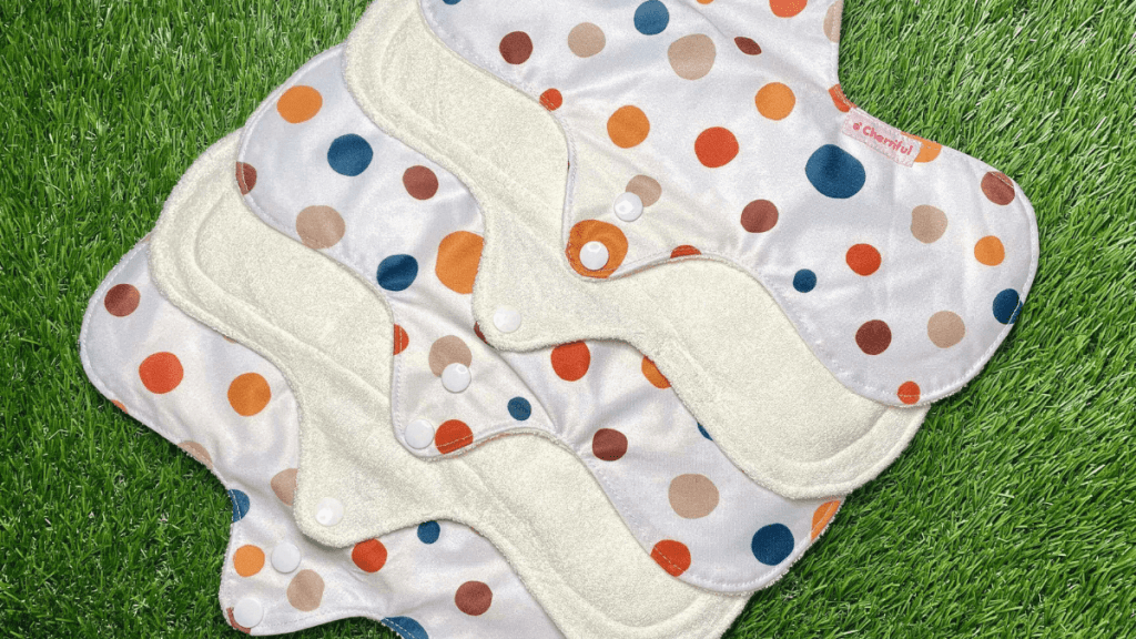 Five Cherriful reusable pads are all resting on grass, slightly overlapping each other. The reusable pads are white with blue, orange, red and beige spots