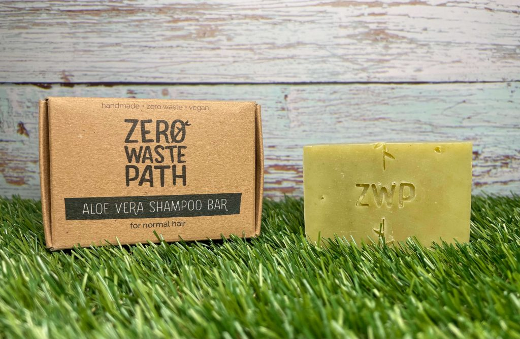 Mental Health Awareness Week Giveaway Goodies! A green rectangle shampoo bar and cardboard box are sat on grass against a blue wooden fence