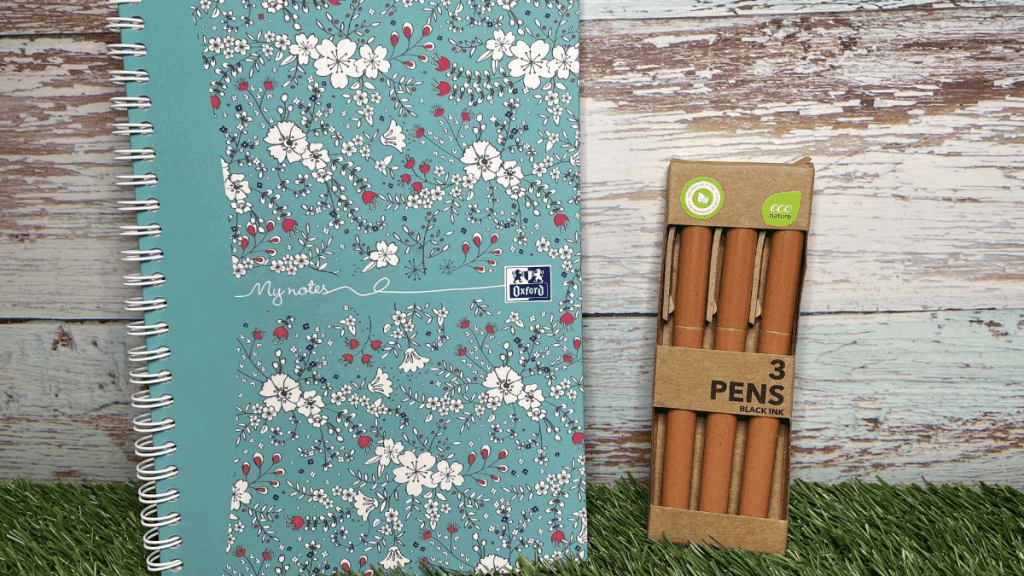 The Mental Health Awareness Week Giveaway Goodies - A green Journal with white, red and black flowers and 3 brown pens in brown cardboard packaging are sat on grass against a blue wooden fence