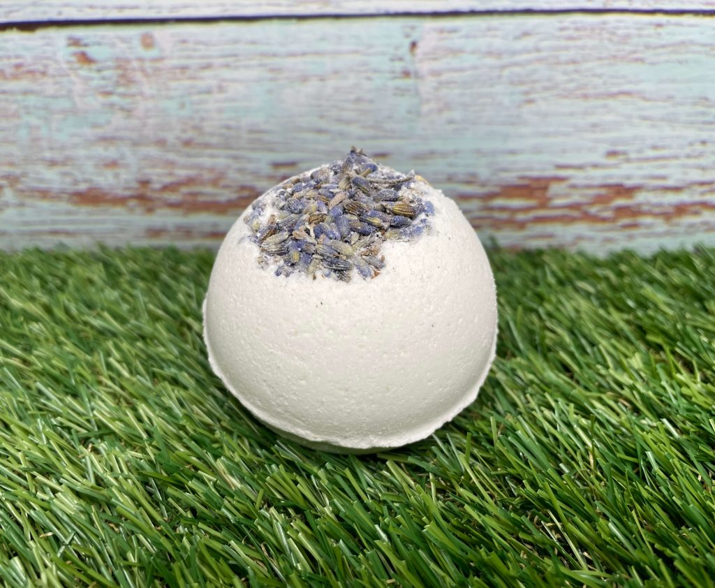 Mental Health Awareness Week Giveaway Goodies! A white bath bomb with dried lavender on top is sat on grass against a blue wooden fence