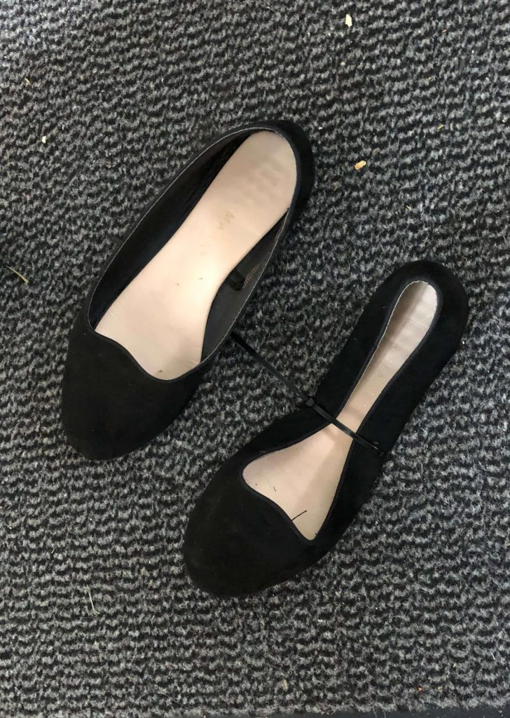 A pair of black dolly shoes are on a black and grey carpet. There is a zip tie pulled tight around one of the shoes