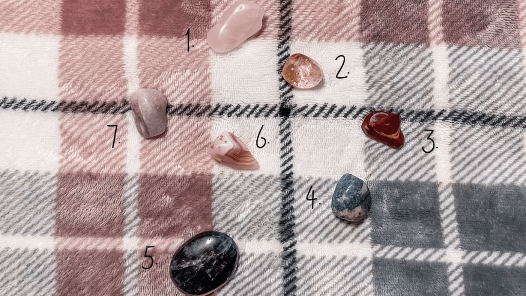 On a pink, white and grey checkered blanket are a small selection of healing crystals.