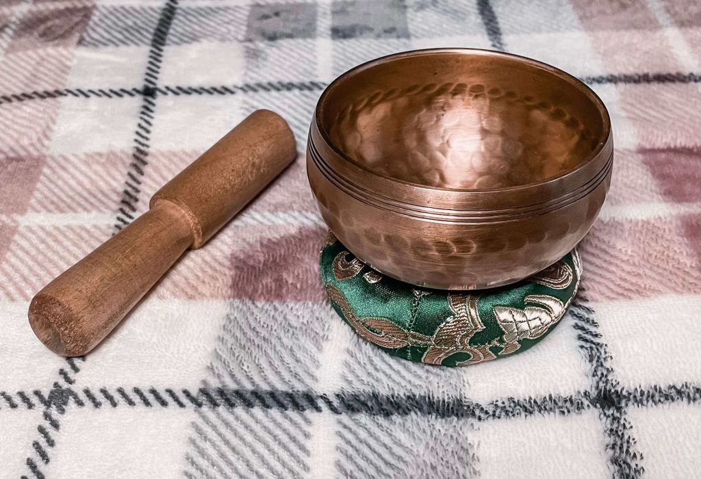 On a pink, white and grey checkered blanket is a Himalayan gupla singing bowl. It is resting on a green and gold ring cushion
