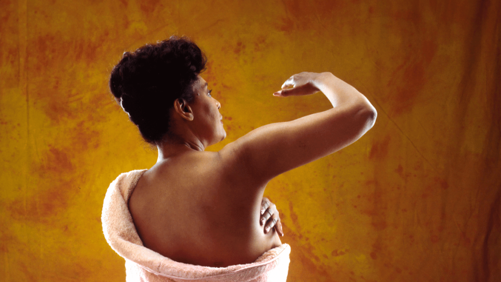 A woman is standing in a pink towel with her back to us. She has her arm raised and is checking her breasts for cancer. She is stood infront of an orange background