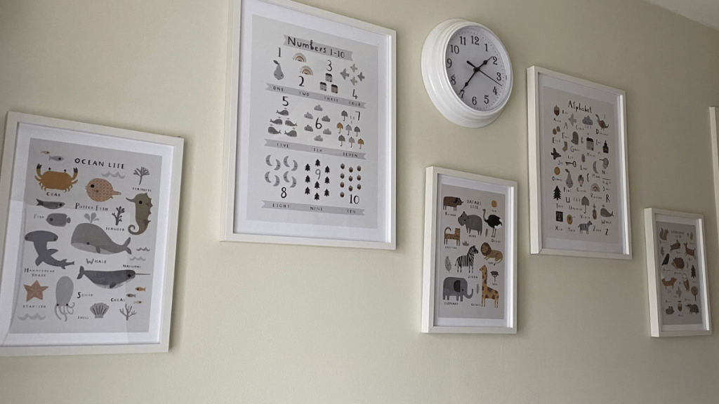 On a wall, there are 5 frames. Two large and 3 smaller. Within the smaller frames are three different prints with animals drawn on them and their names underneath. There is Ocean Life, Safari Life and Woodland Life. The larger frames are numbers 1 - 10 with different objects and the alphabet with different pictures for each letter
