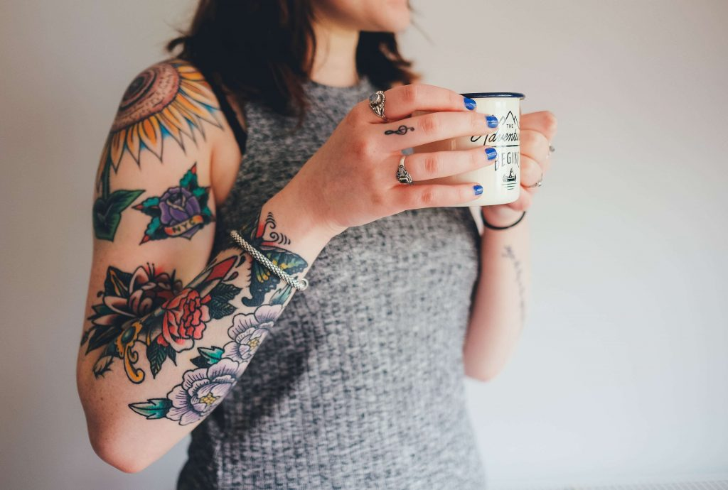 A woman with brown hair is holding a mug. She is wearing a grey sleeveless top and has a silver bracelet on she has several brightly coloured tattoos on her arm